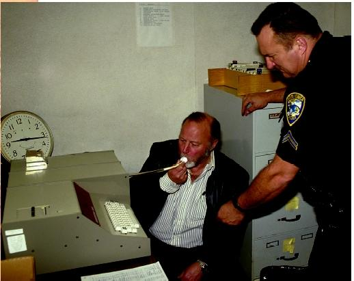A Santa Monica police officer administers a breathalyzer test to a man to determine the alcohol level in his bloodstream.
