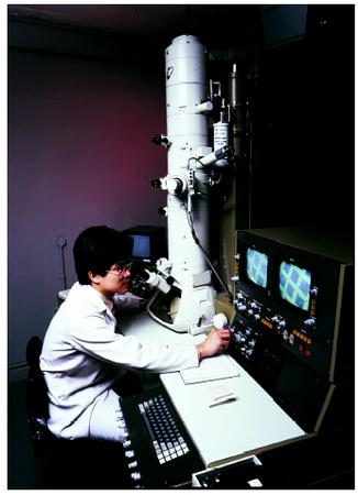 A scientist operating a scanning transmission electron microscope.